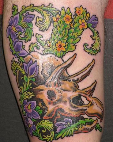 Dinosaur skull in green flower tracery tattoo