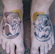 Two coloured dogs tattoo on feet