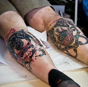 Two dogs on boths legs coloured tattoo