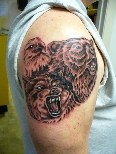 lupo agressivo ed orso sulla spalla tatuaggio