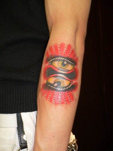 Symmetrical eyes arm tattoo