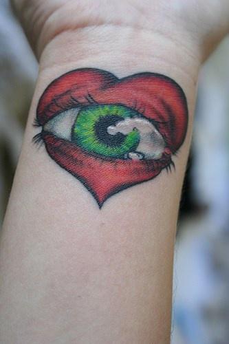 cuore rosso con occhio sul polso tatuaggio