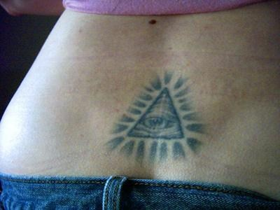 All seeing eye tattoo on lower back