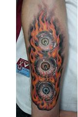 bulbo oculare colorato con fiame tatuaggio sul braccio
