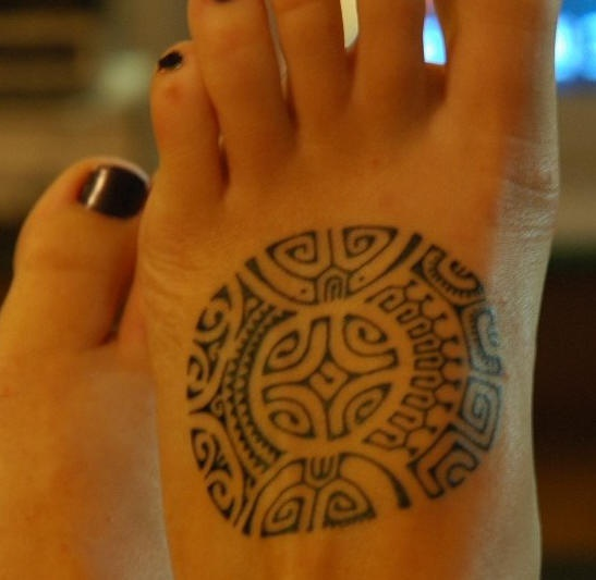 Ornamento in forma rotonda tatuato sul piede