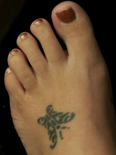 Little black sign-butterfly foot tattoo