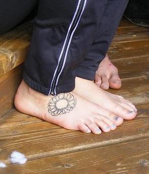 Round uncoloured flower foot tattoo