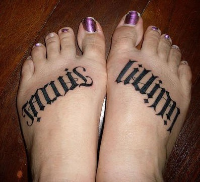 Black styled with little rhombs inscription foot tattoo