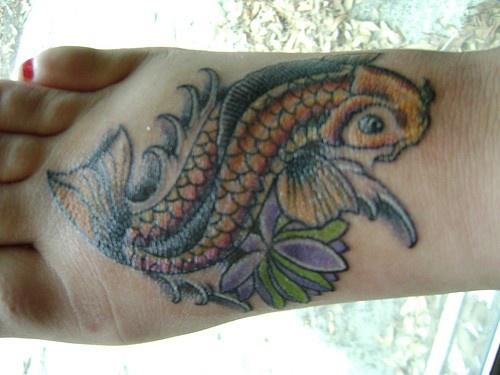 Grande tatuaggio variegato sul piede pesce e fiore
