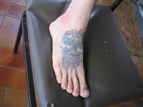 Angry skull with opened teeth foot tattoo