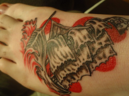 Ship sails in red waves foot tattoo