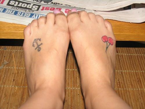 Piccola nera ancora e ciliegie tatuate sui piedi