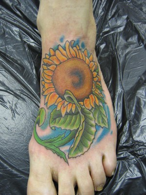 Fine sunflower with juicy leaves foot tattoo