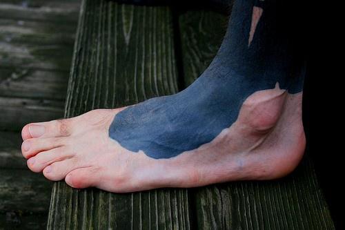 Black shade adornment foot tattoo