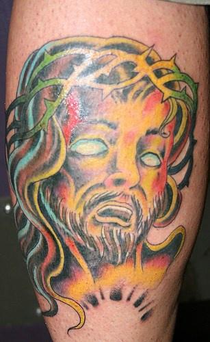 Parti-coloured jesus in despair, forearm tattoo