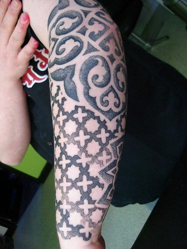 Parti-coloured pattern, orbed crosses , curls forearm tattoo