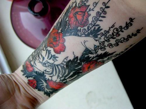 Tatuaje en el antebrazo, gato blanco en el campo de amapolas