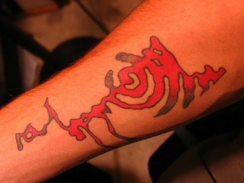 Red image, piece of labyrinth forearm tattoo