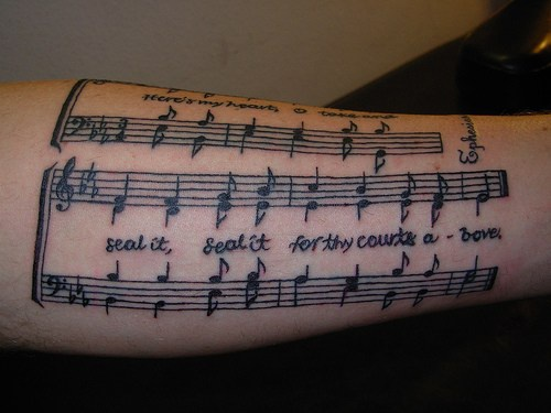 Sheet music, text of song forearm tattoo