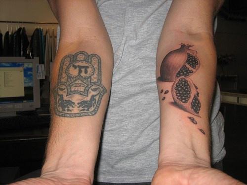 Disegno e melagrana tagliata tatuati sui bracci