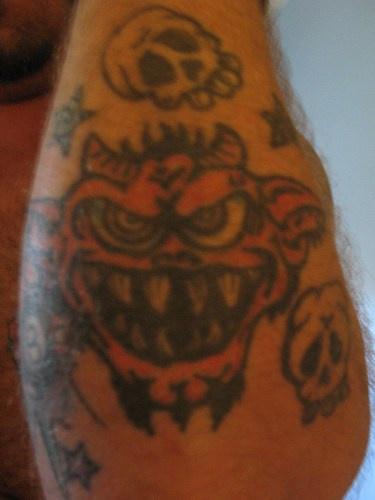 Spaventoso mostro e teschio tatuati sul braccio