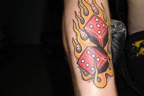 Dadi in fuoco tatuati sul braccio
