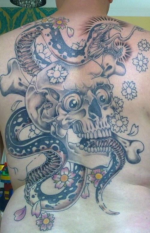 Cattiva scena serpente e il teschio con le ossa tatuati sulla schiena