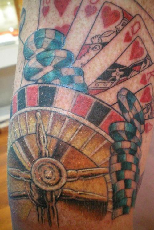 Roulette wheel with royal flush of hearts tattoo