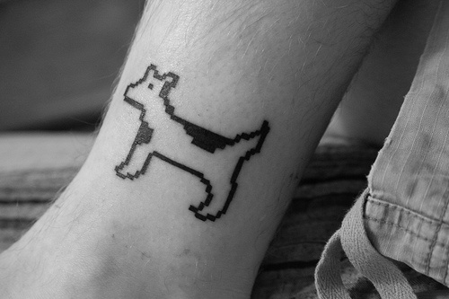 Eight bit style dog tattoo on hand