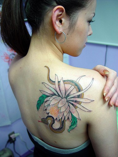 Elegant flower and snake on shoulder