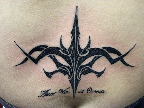 Black tribal tracery on lower back