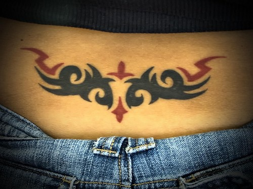 Black and red tribal tracery on lower back