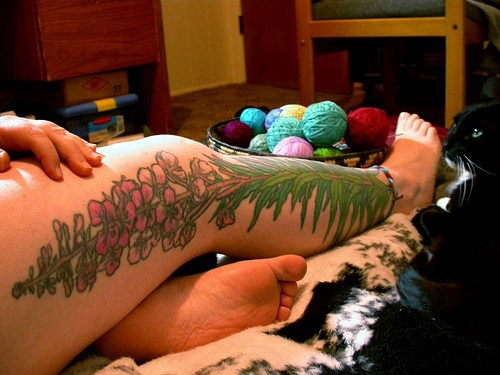 Large plant with pink flower tattoo on whole leg