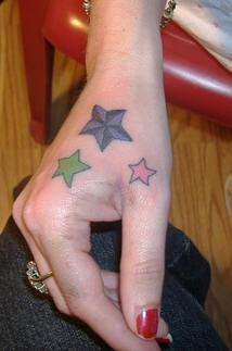 Le stelle colorate tatuate sulla mano della donna