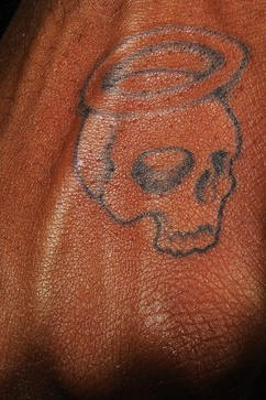 Colourless part of skull with nimbus hand tattoo