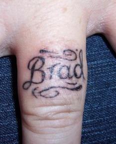 Brad, name inscription on one finger hand tattoo