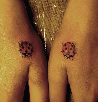 Two little colourful ladybird hand tattoo
