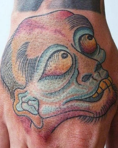 Ugly creature with big eyes hand tattoo