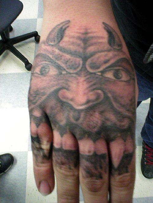 Awful, horned devil, sharp teeth hand tattoo