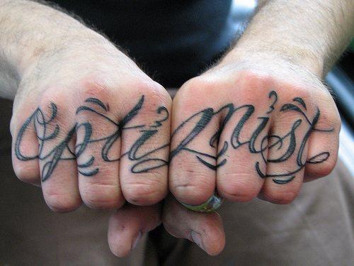 Optimist ,curled styled  inscription, hand tattoo