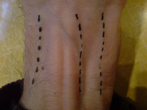 Dotted lines on veins tattoo