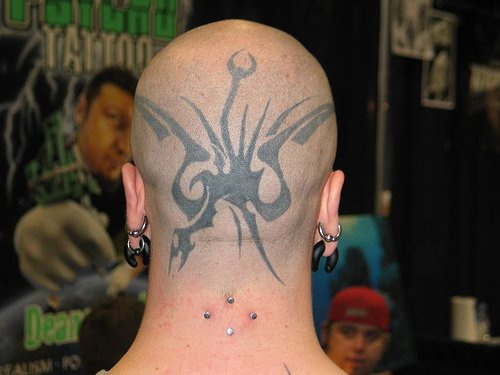 Head tattoo with black, flying monster dragon