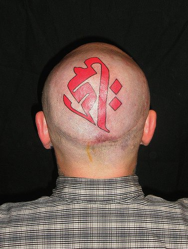 Head tatoo,big,  bright styled, red sign-hieroglyph