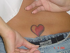 Small red heart tattoo on lower back - Tattooimages.biz