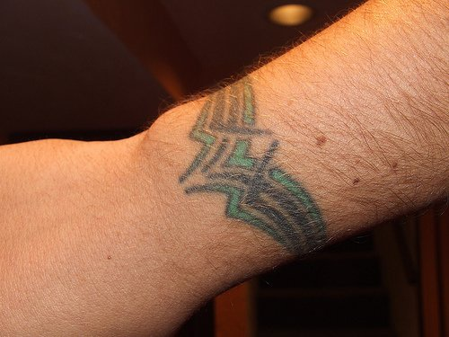 Coloured tracery wrist tattoo