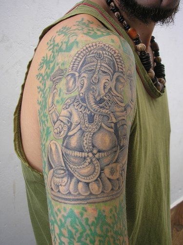 Blue ganesha in rest with hindu pattern tattoo