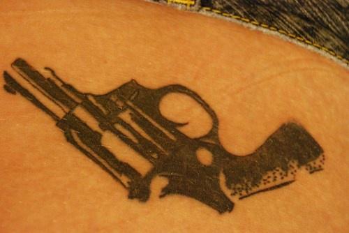 Big, black, realistic gun hip tattoo