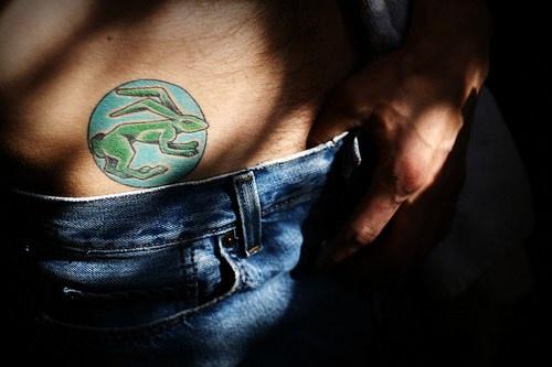 Green hear in blue circle hip tattoo