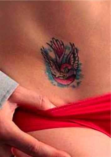 Shouting, colourful, flying bird hip tattoo