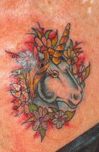 Unicorn head in flowers tattoo